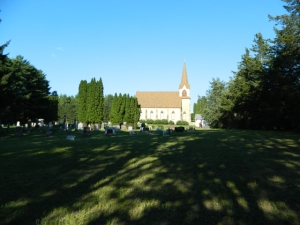 "St. John Lutheran Church and Cemetery, Budsin (mailing address Neshkoro). According to ""A Historical Stroll through the Churches of Marquette County"" (1985), ""a wooden frame church was built facing our now Highway 22 on the cemetery grounds west of the present brick church"" - the foreground of this picture. This would have been the closest church to the parsonage where Pastor Strieter lived. It is thus considered the mother church of all the other confessional Lutheran churches in the area. The present brick church was built in 1907."